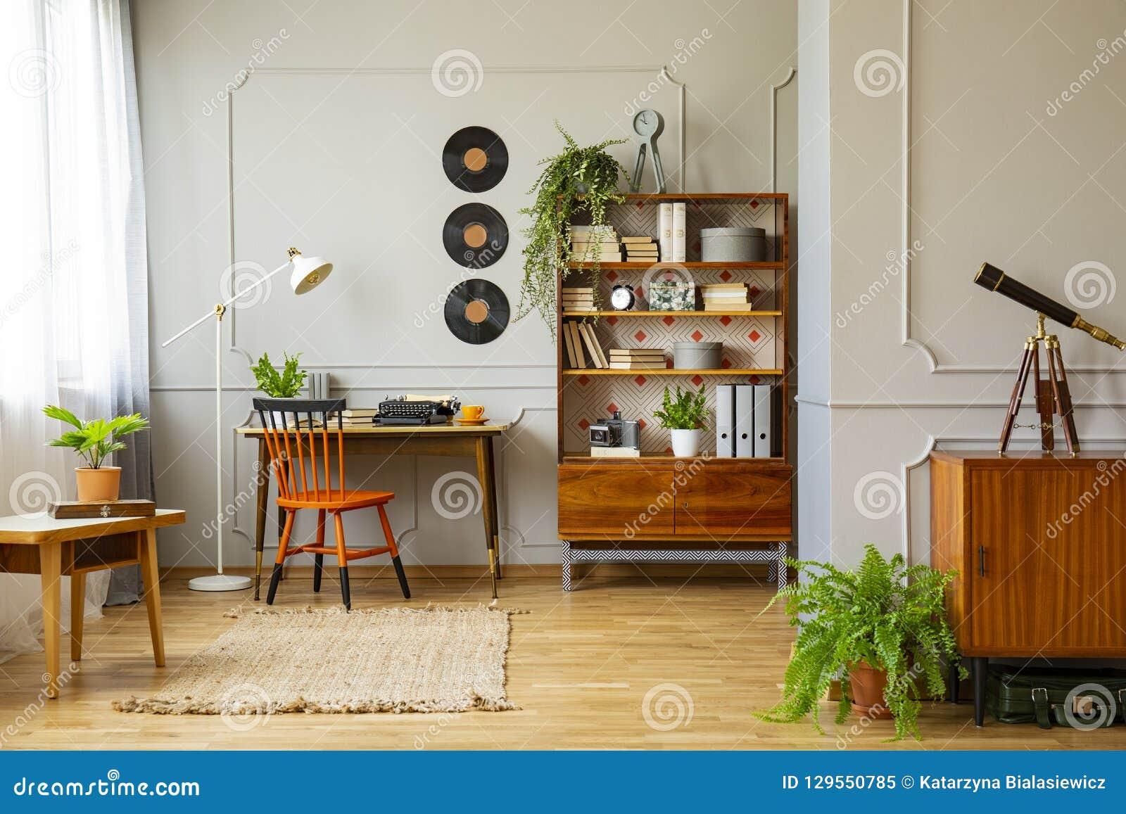 Het vinyl registreert decoratie op een grijze muur met het vormen en houten meubilair in een retro binnenland van het huisbureau