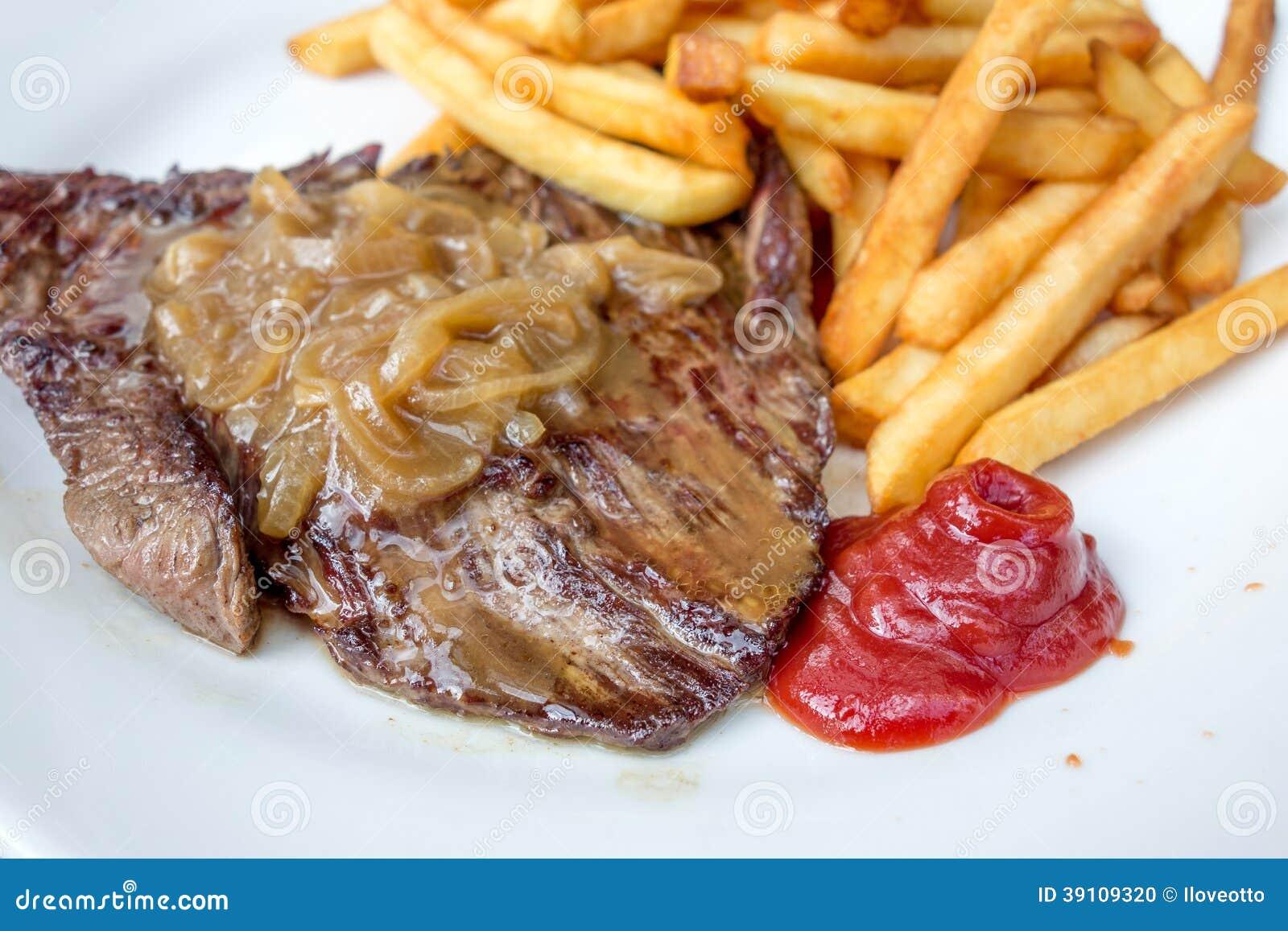Het vlees van het lapje vleesrundvlees met tomaat en frieten