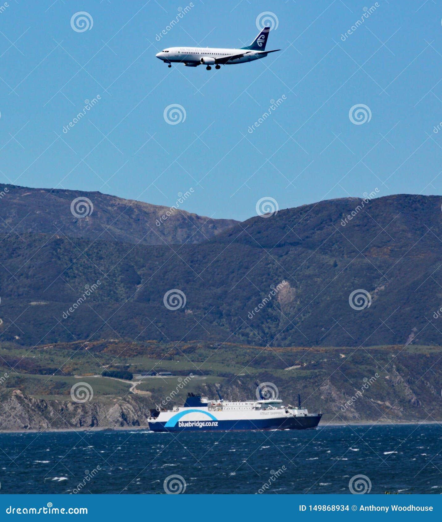Het vliegtuig op definitieve benadering van de luchthaven van Wellington, passen over een Interislander-veerboot op het is manier