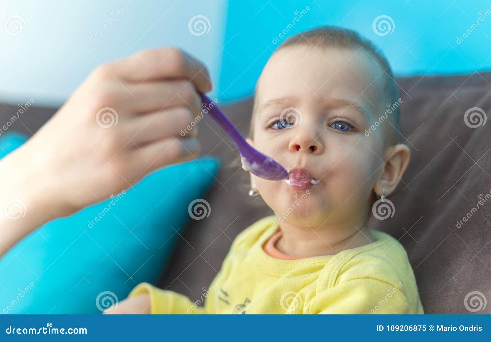 Het voeden van Haar Babymeisje met een Lepel