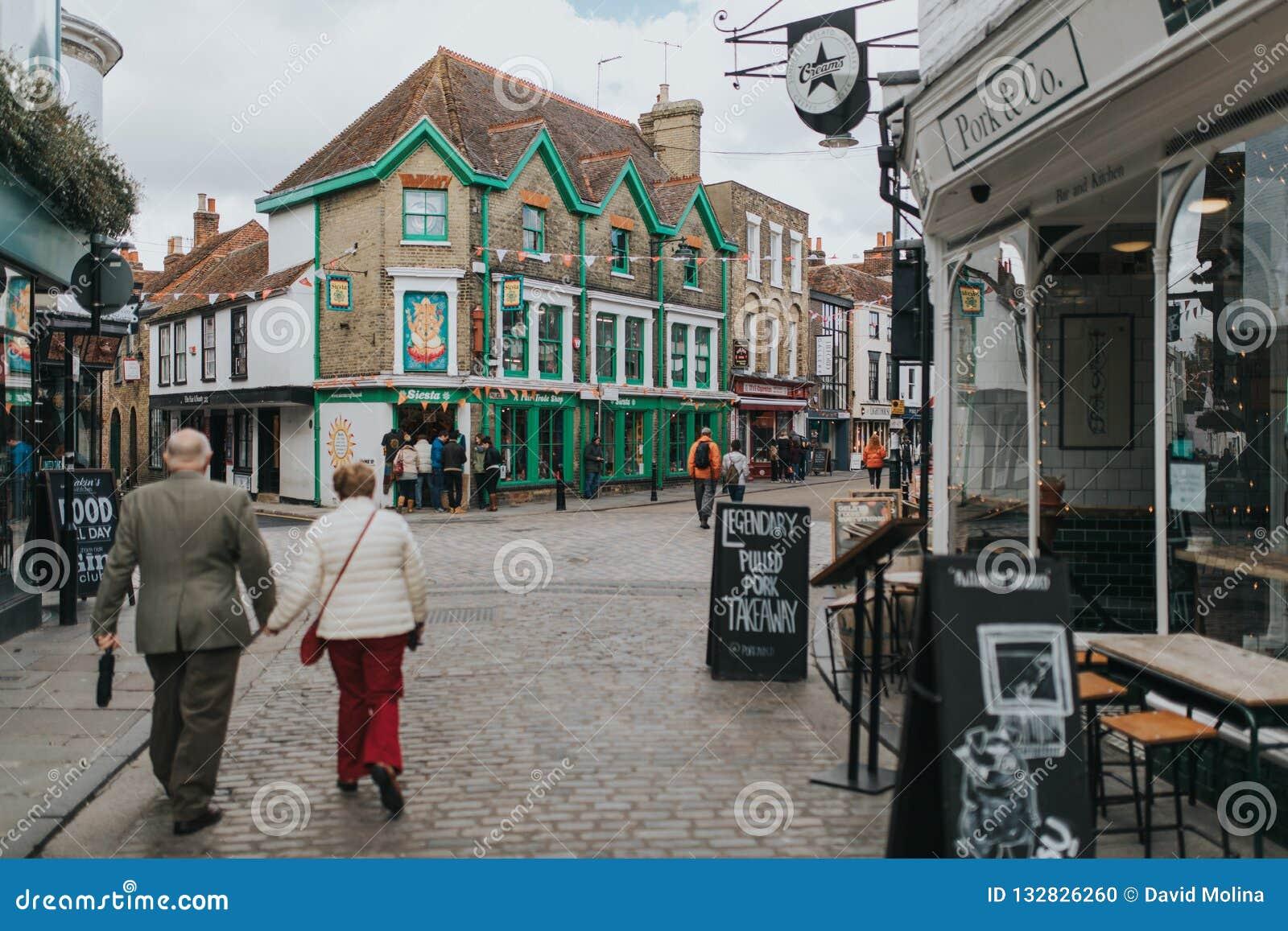 Het voet lopen cobblestoned straat, met winkels rond het, en traditionele architectuur in het dorp van Canterbury,