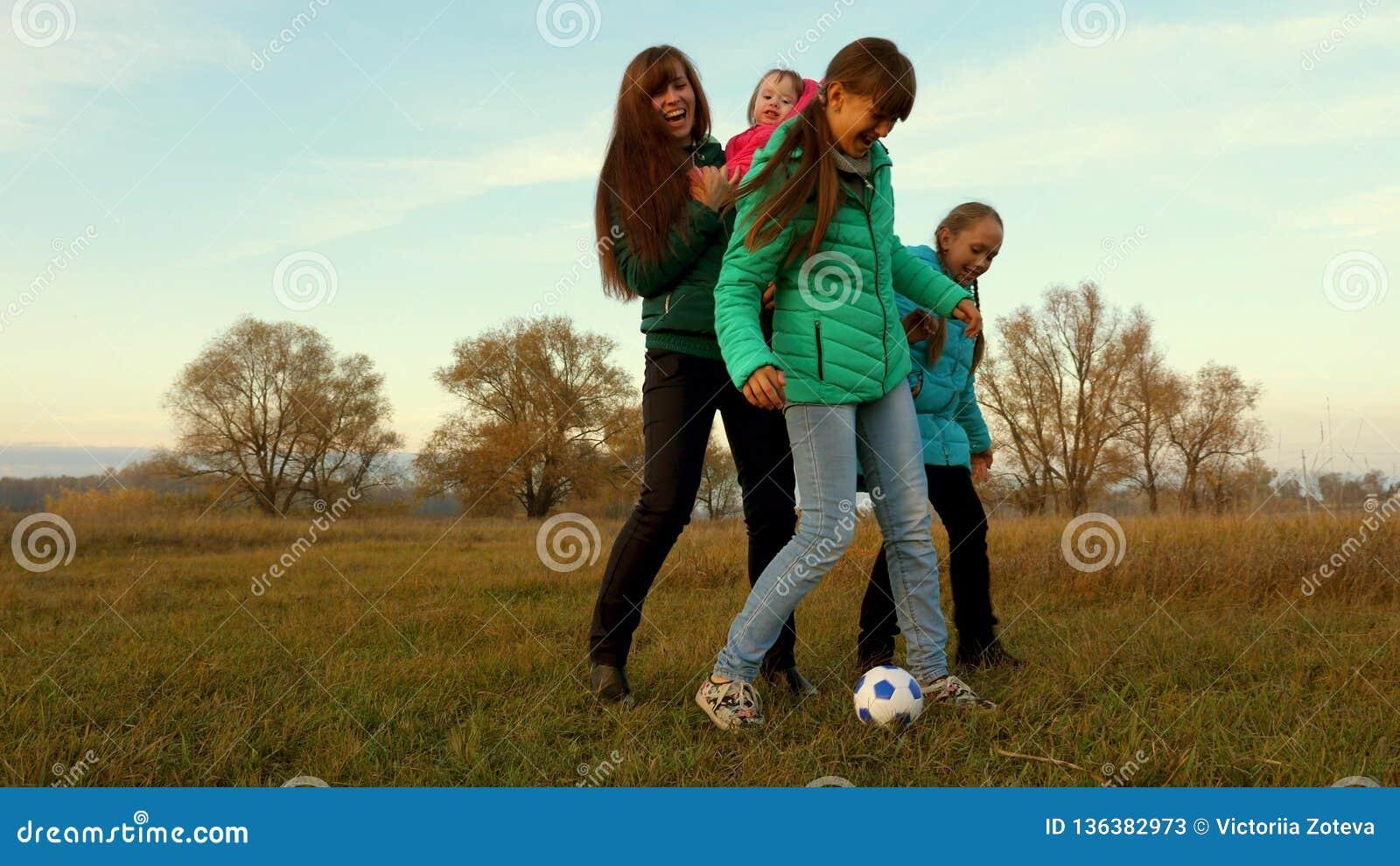 Het voetbalbal van papaschoppen Kinderen en mammaspelvoetbal op gebied Familie het spelen met klein kind door de bal van kinderen