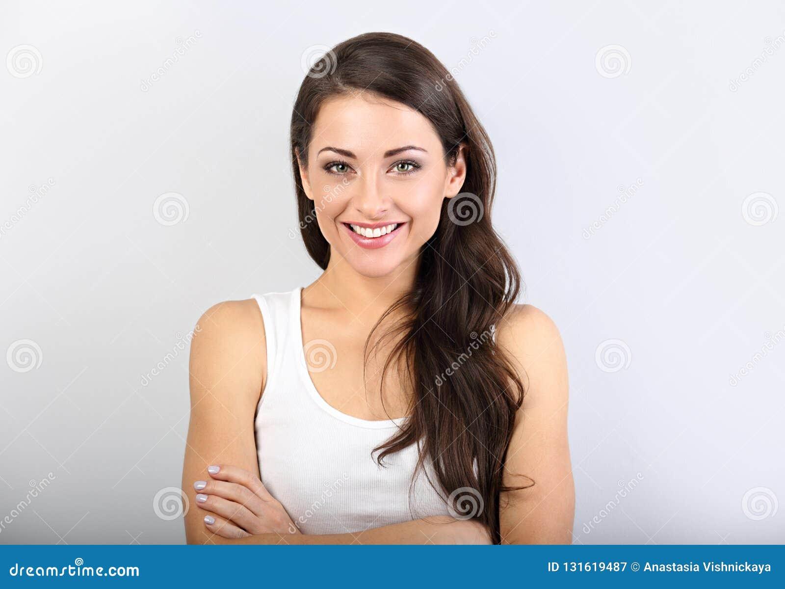 Het vooraanzicht van mooie vrouw met naakte make-up en gezond glanst huid kijkend met gevouwen wapens