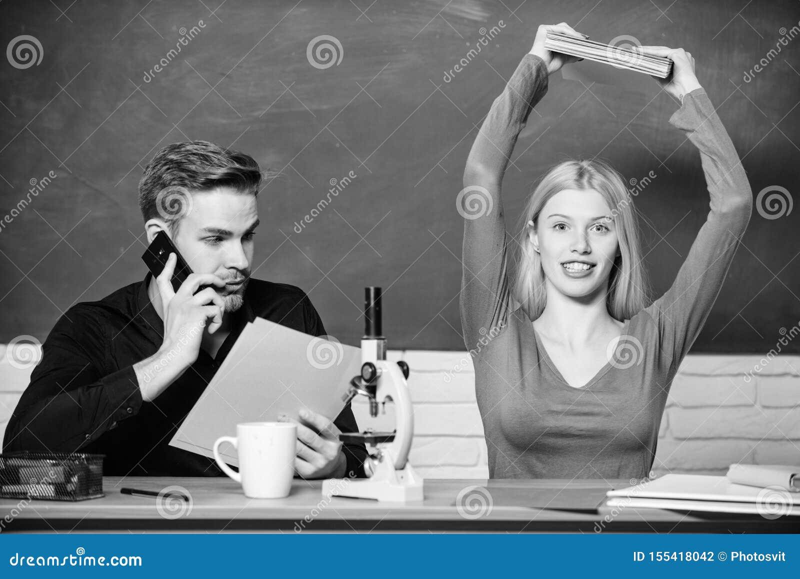 Het voorbereiden van een les Mooie leraar en knappe schoolmeester die documenten sorteren Universiteit of studenten Paar