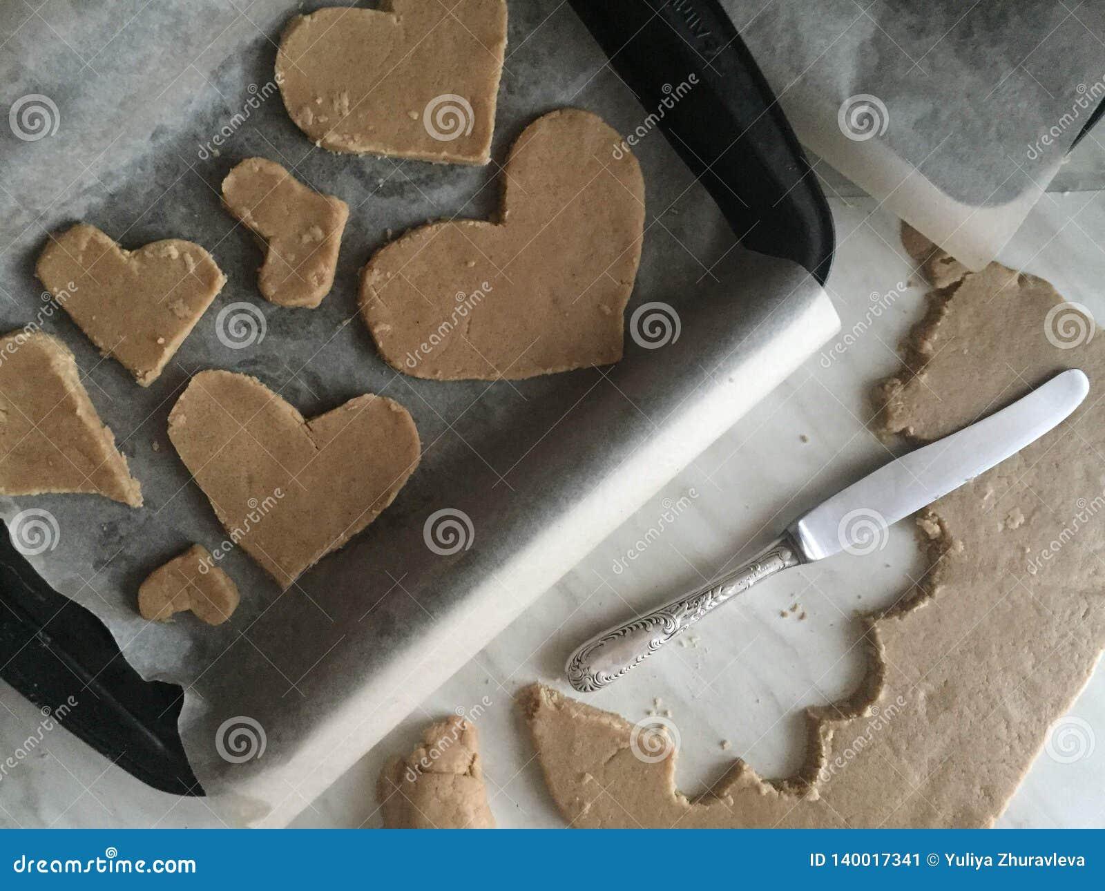 Het voorbereiden van gemberkoekjes verwijdert het oude mes in de vorm van een hartkoekjes