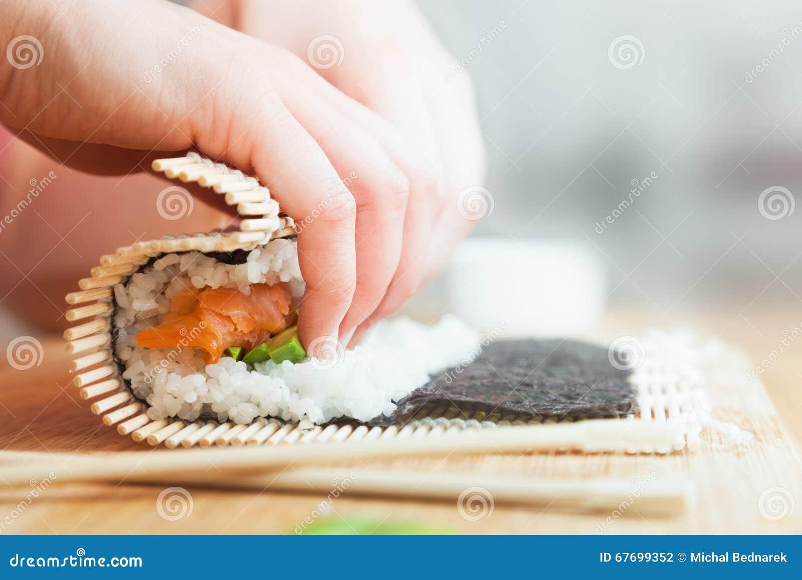Het voorbereidingen treffen, rollende sushi Zalm, avocado, rijst en eetstokjes op houten lijst