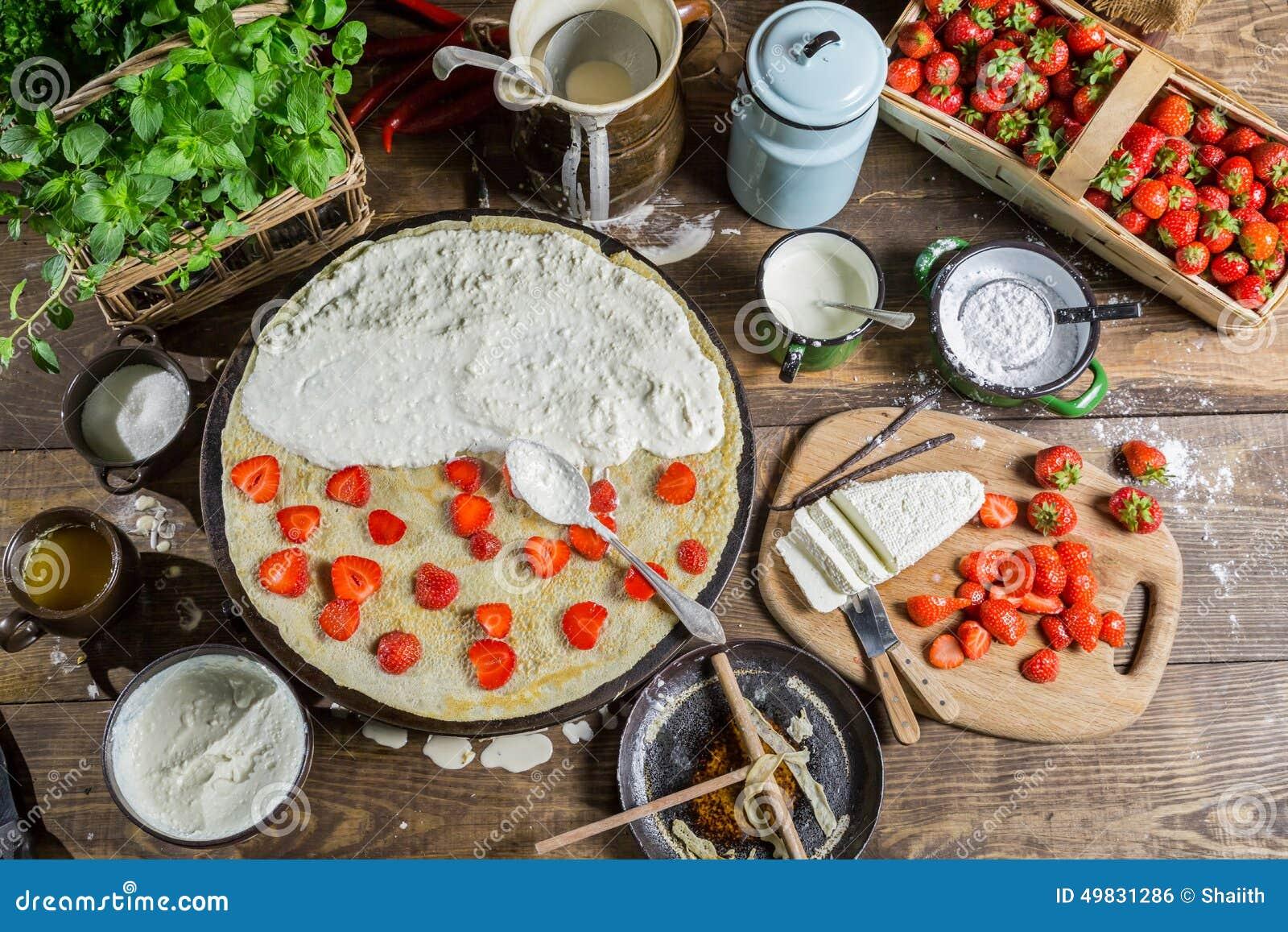 Het voorbereidingen treffen voor pannekoeken met aardbei