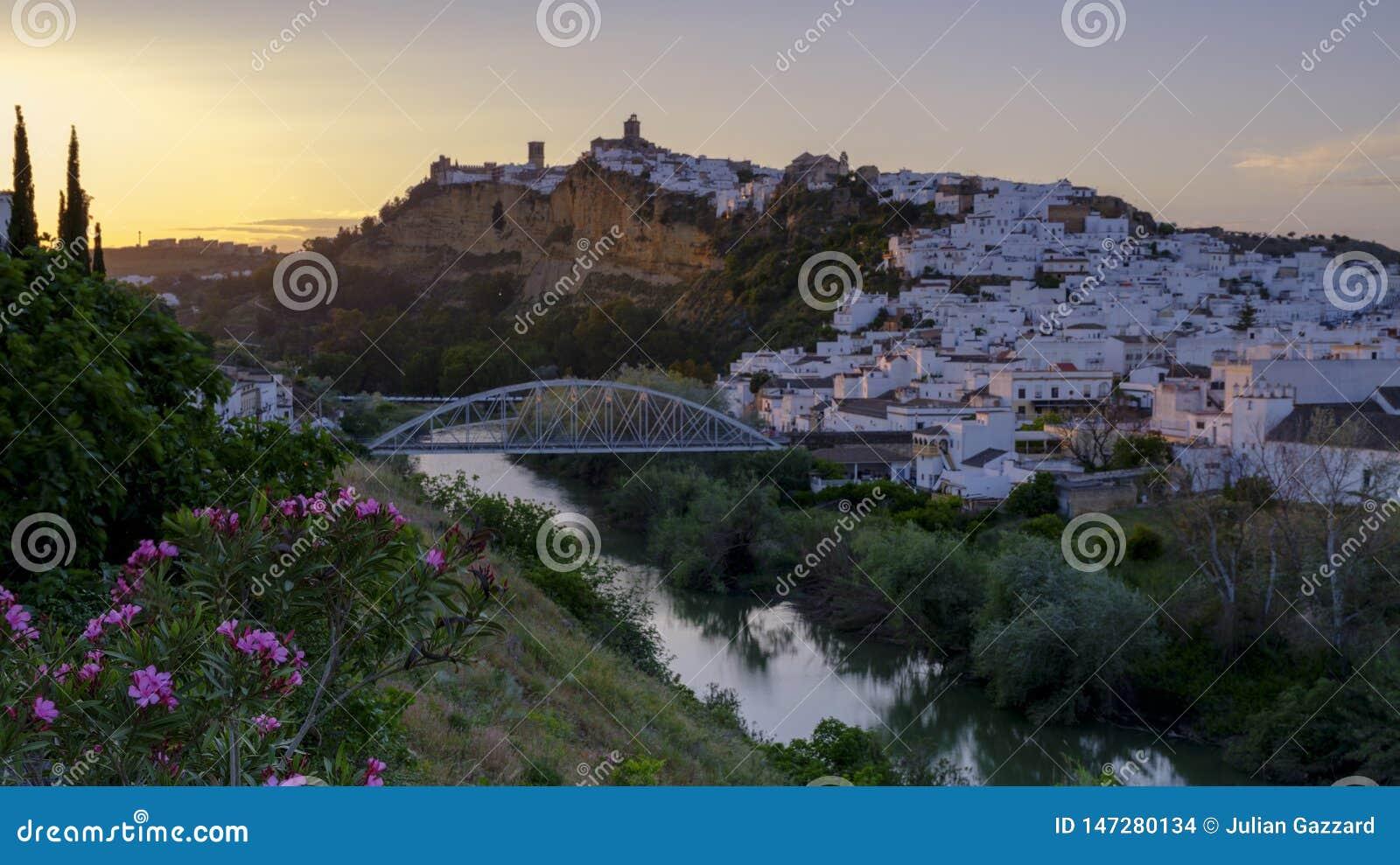 Het vroege avondzonsondergang lichte vallen op de stad van Arcos de la Frontera, Andalucia, Spanje