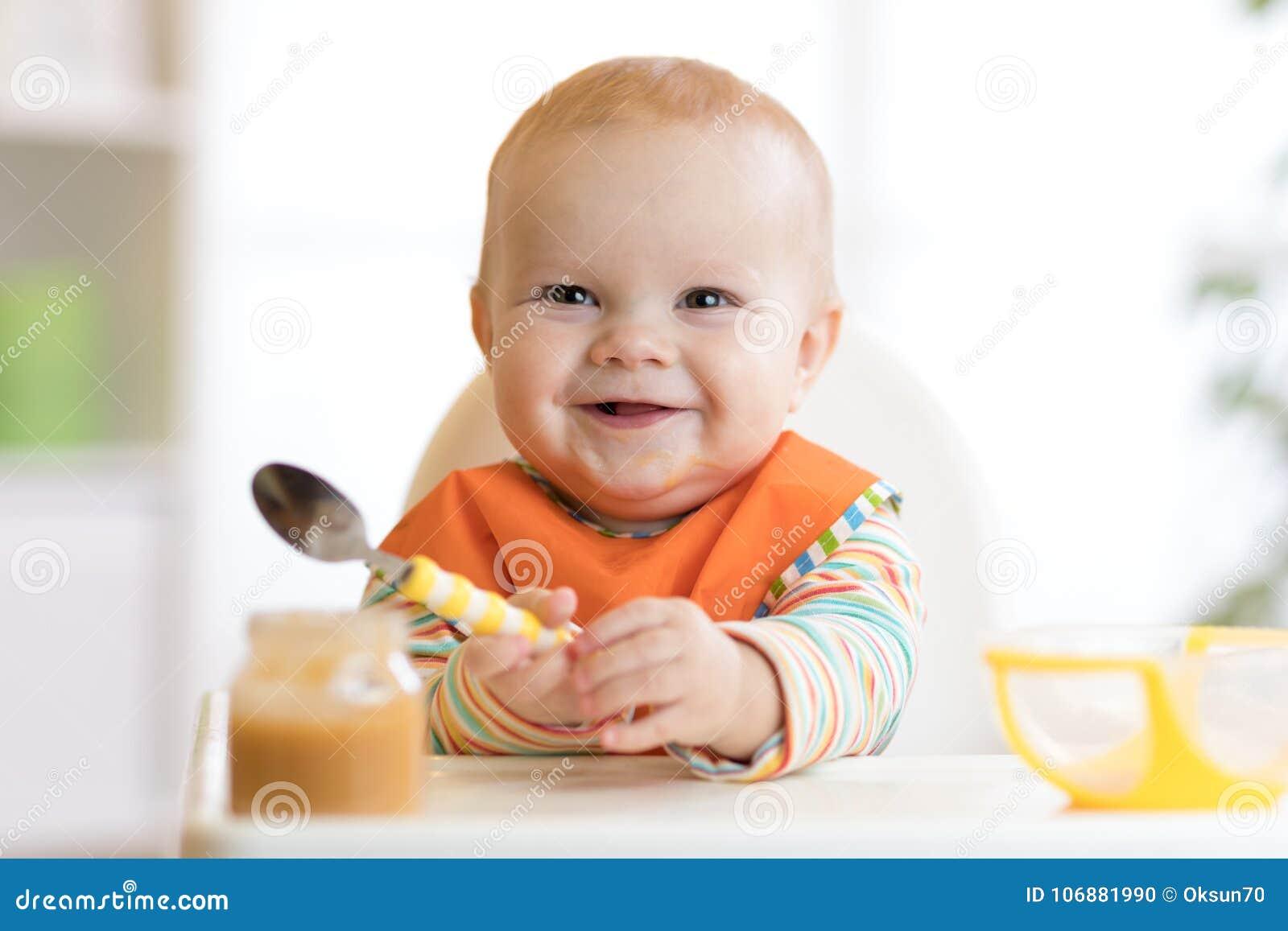 Het vrolijke babykind eet voedsel zelf met lepel Portret van gelukkige jong geitjejongen in hoog-stoel