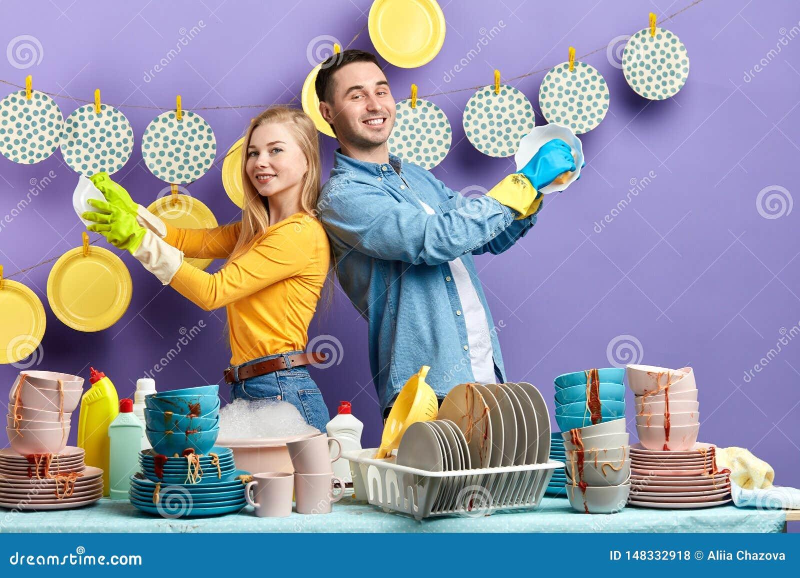 Het vrolijke gelukkige familie genieten die in de keuken werken