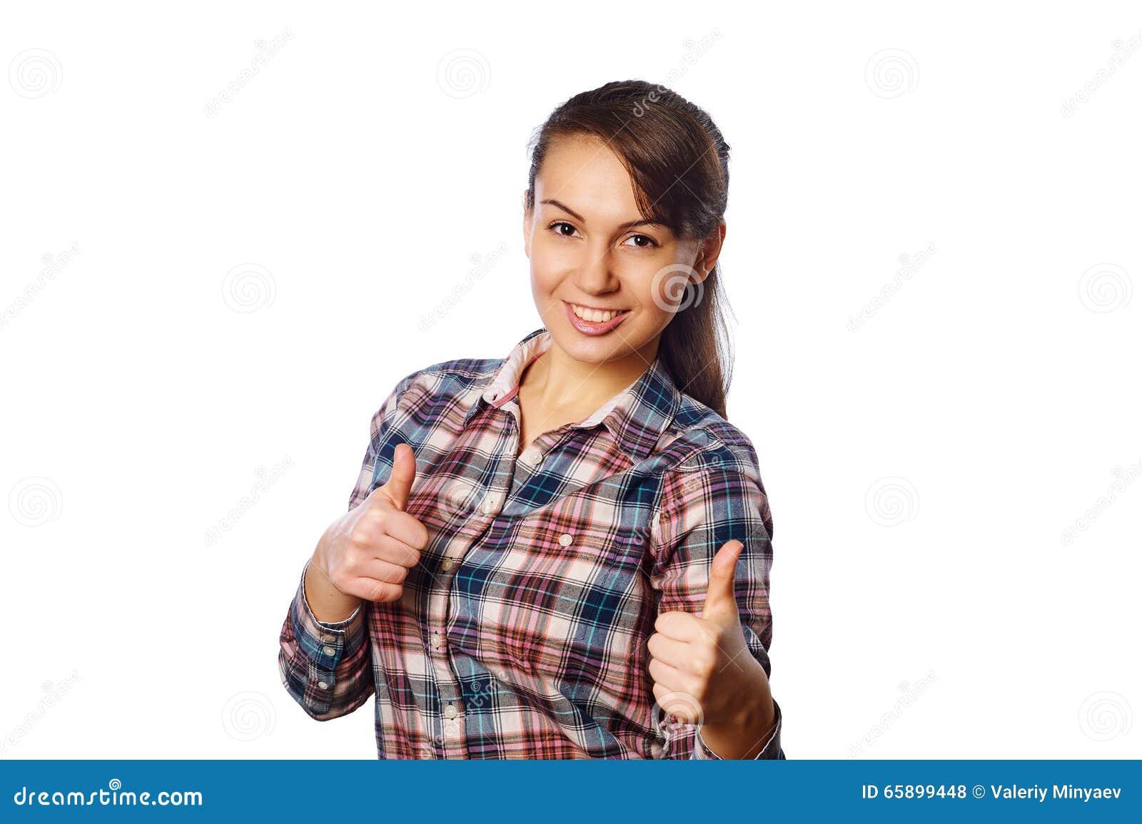 Het vrolijke jonge meisje in geruit overhemd die duimen met allebei tonen overhandigt omhoog witte achtergrond