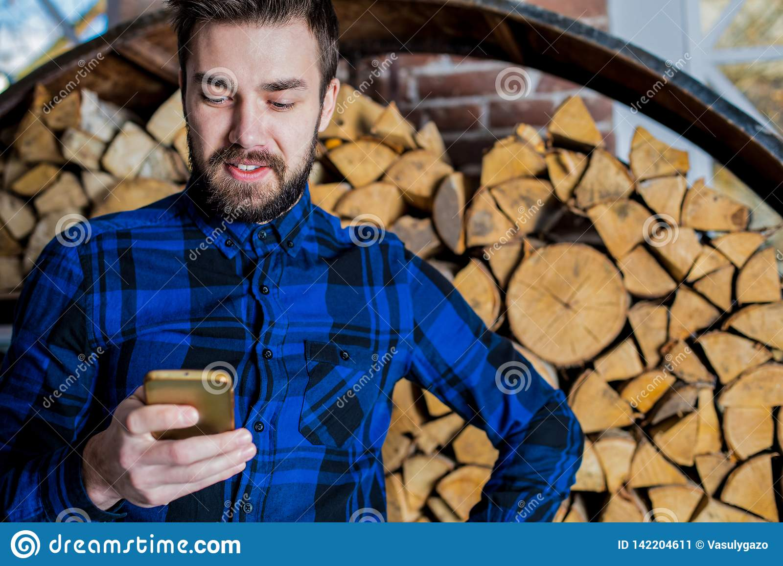 Het vrolijke mannelijke babbelen in Internet op celtelefoon Modieuze mens die cellphone gebruiken