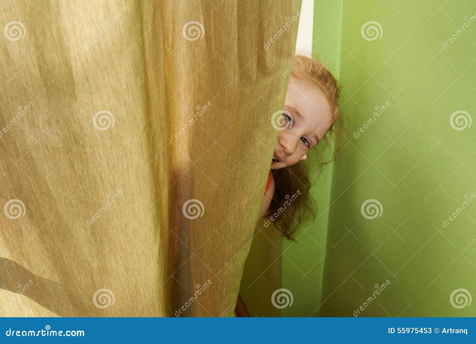 Het Vrolijke Meisje Kijkt Uit Van Achter Gordijnen Stock Afbeelding ...