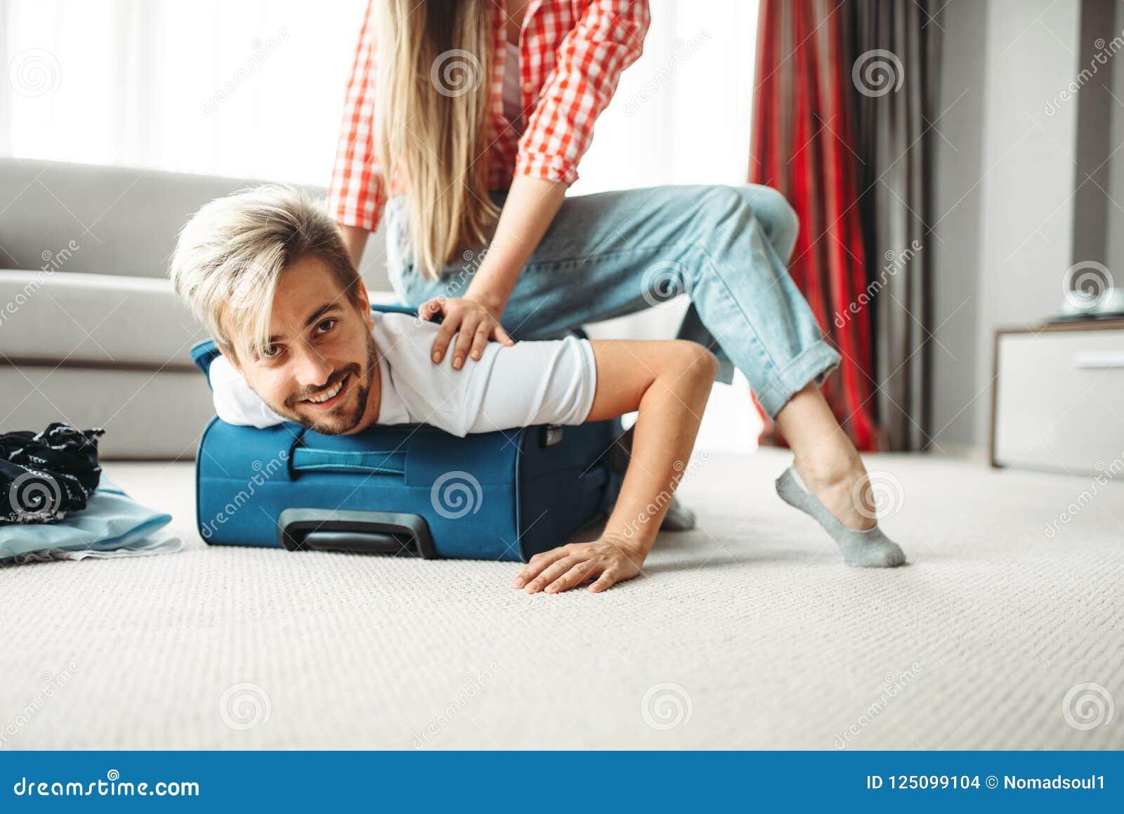 Het vrolijke meisje pakte haar echtgenoot in een koffer in