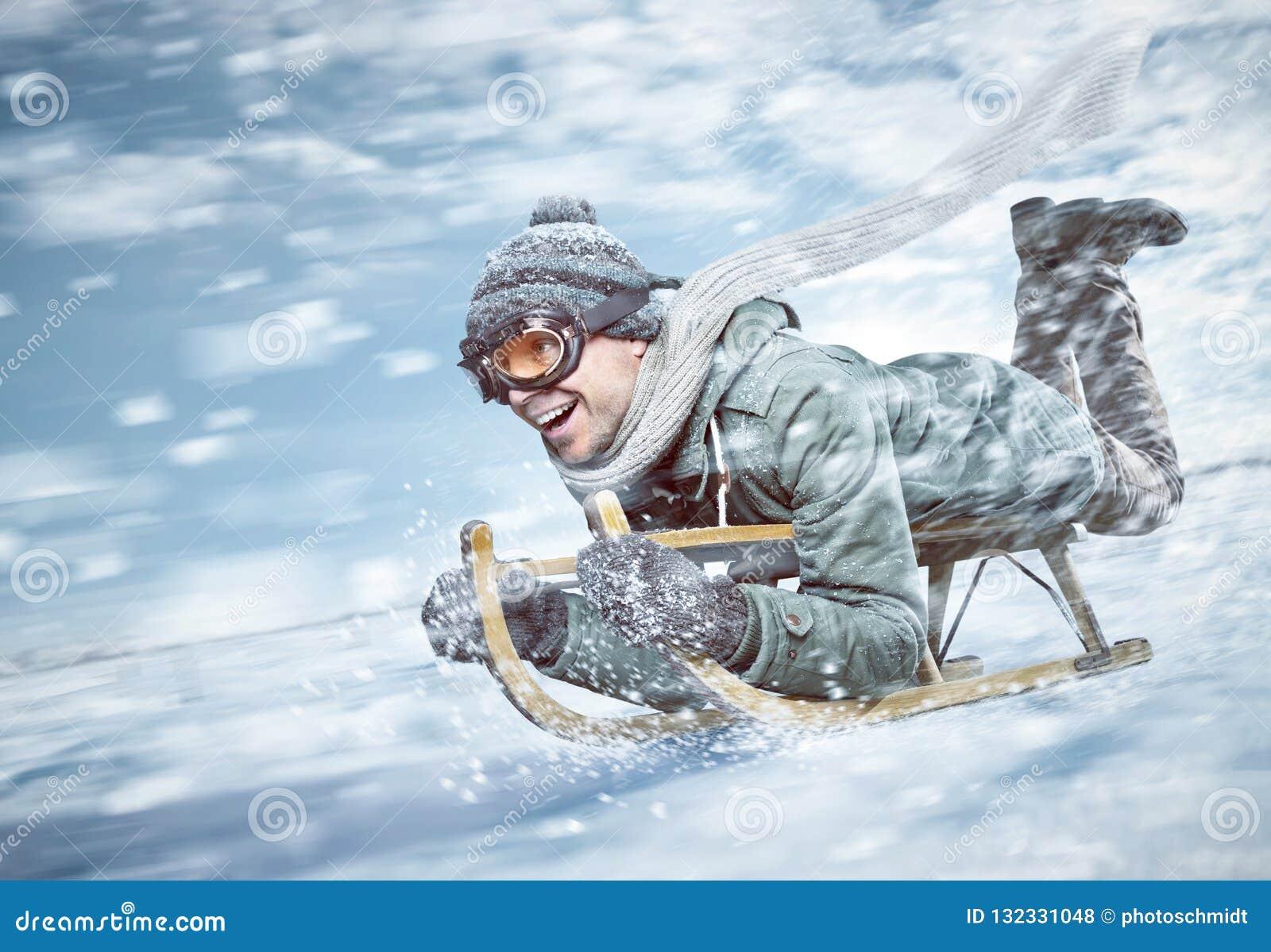 Het vrolijke mens sledding onderaan een sneeuwhelling in volledige snelheid