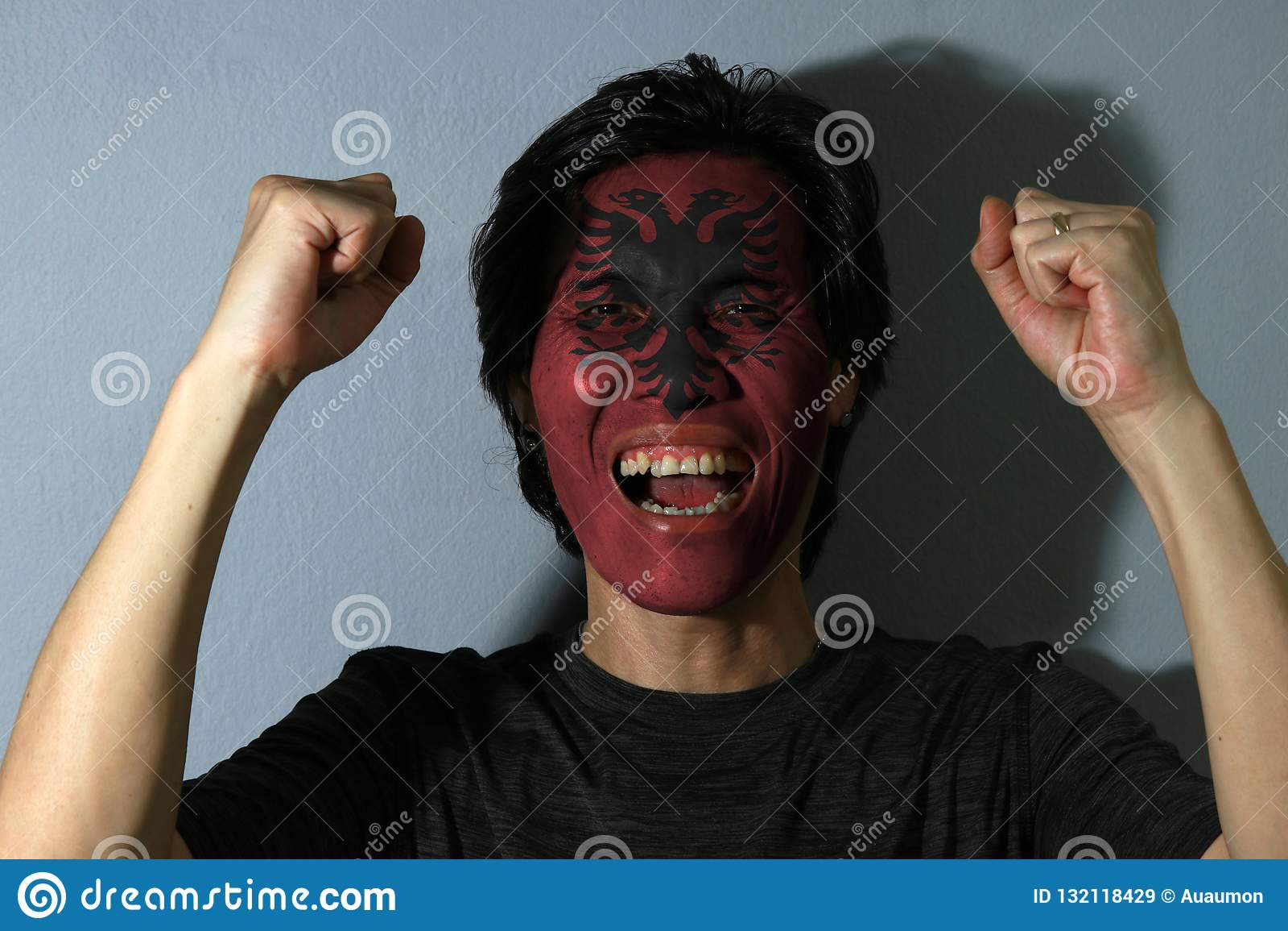 Het vrolijke portret van een mens met de vlag van Albanië schilderde op zijn gezicht op grijze achtergrond