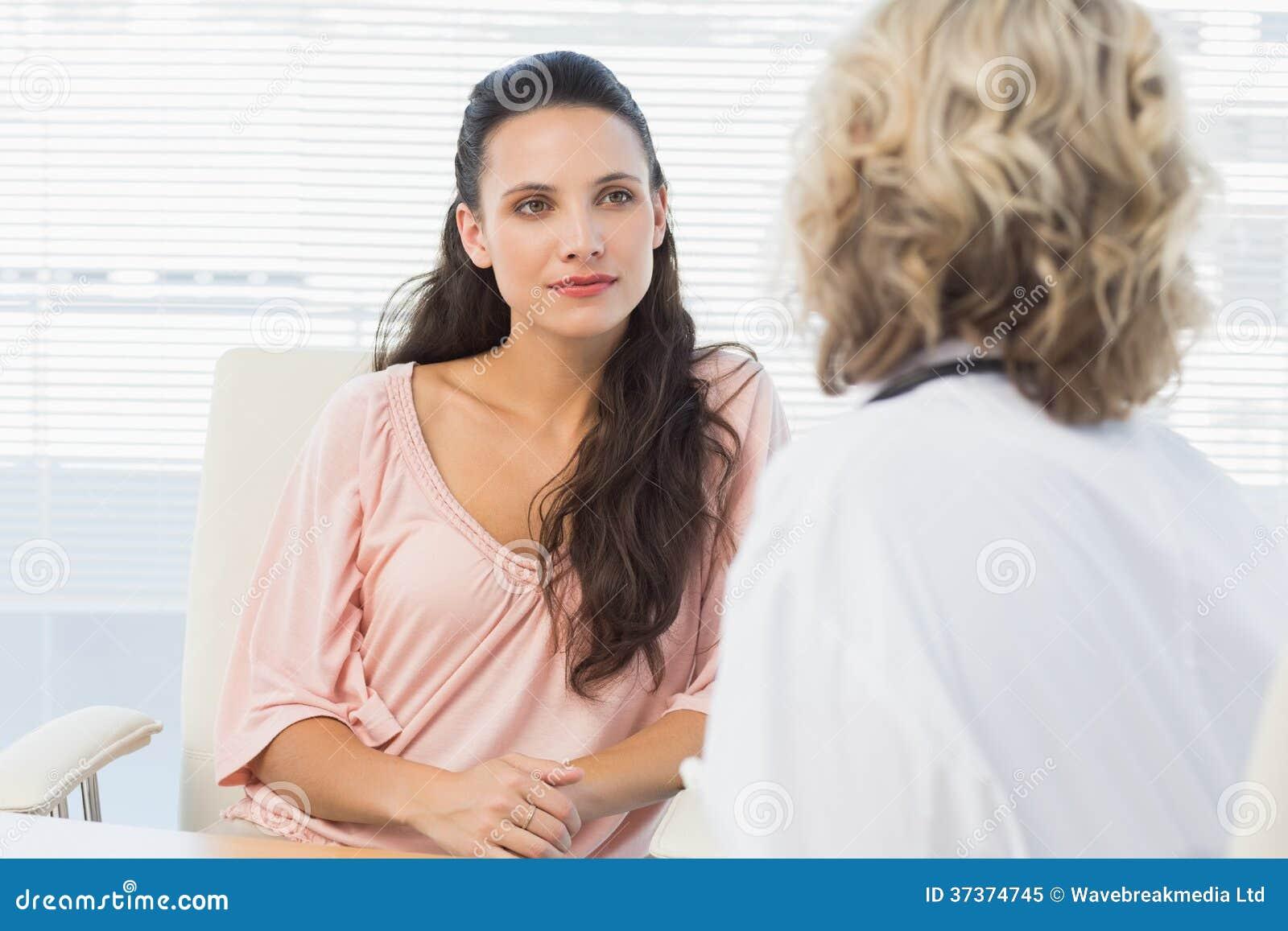 Het vrouwelijke geduldige luisteren aan arts met concentratie in medisch bureau