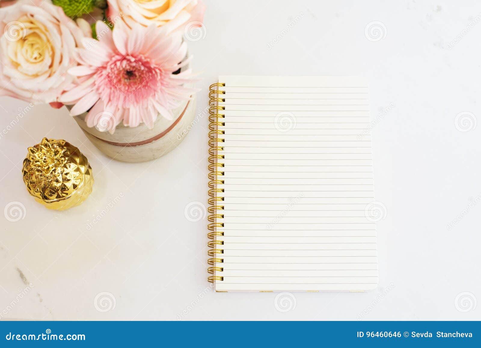 Het vrouwelijke werkplaatsconcept in vlakte legt stijl met bloemen, gouden ananas, notitieboekje op witte marmeren achtergrond Ho