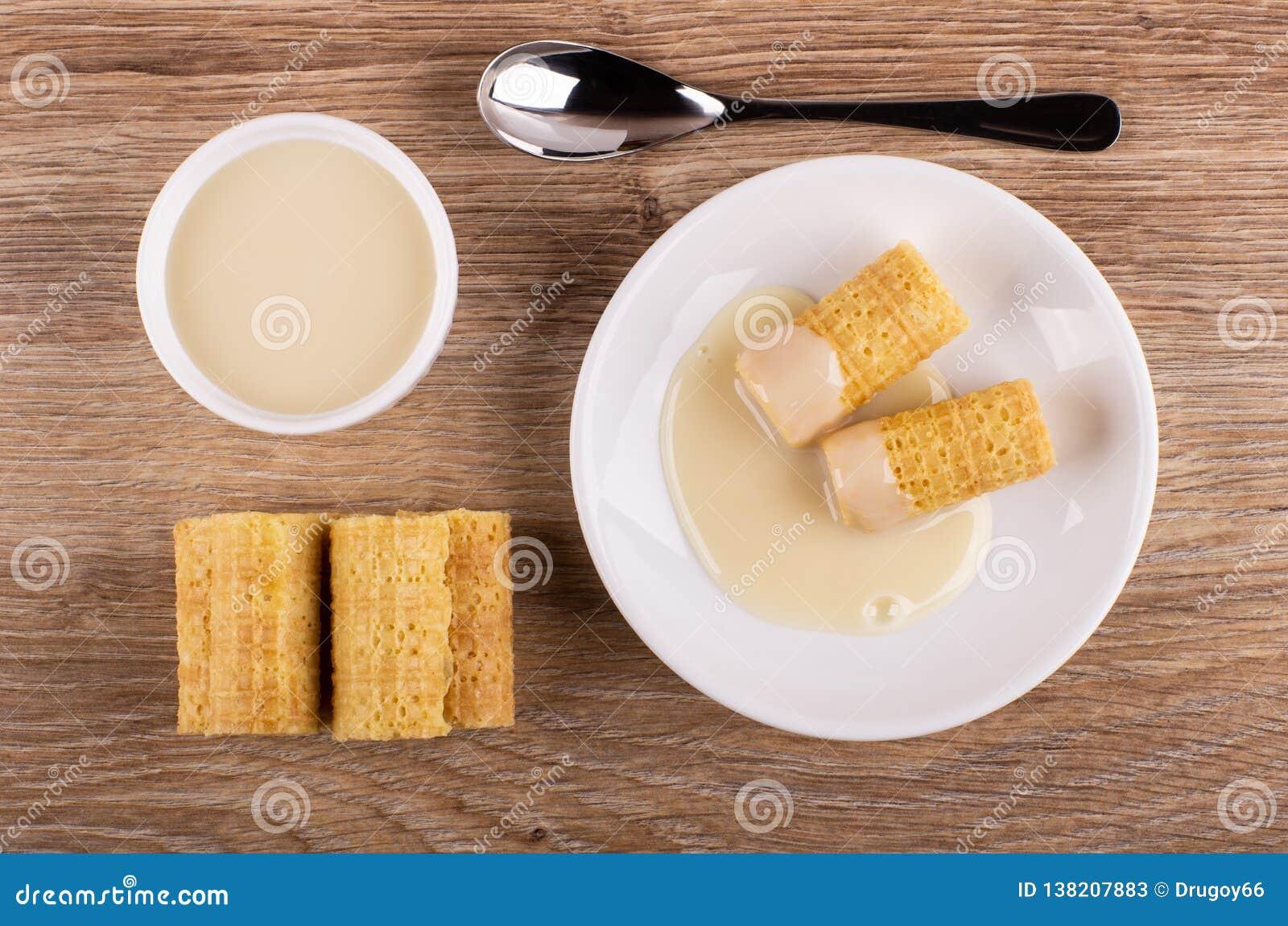 Het wafeltje rolt met condens in schotel, glaskom met melk, lepel op lijst Hoogste mening