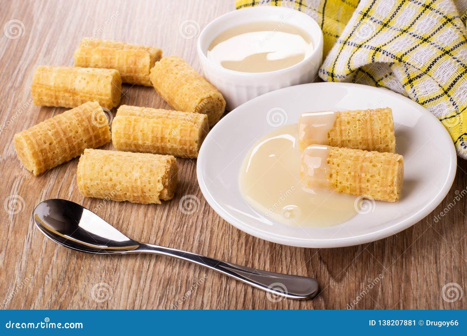 Het wafeltje rolt met condens in schotel, lepel, kom met melk, servet, broodjes op lijst