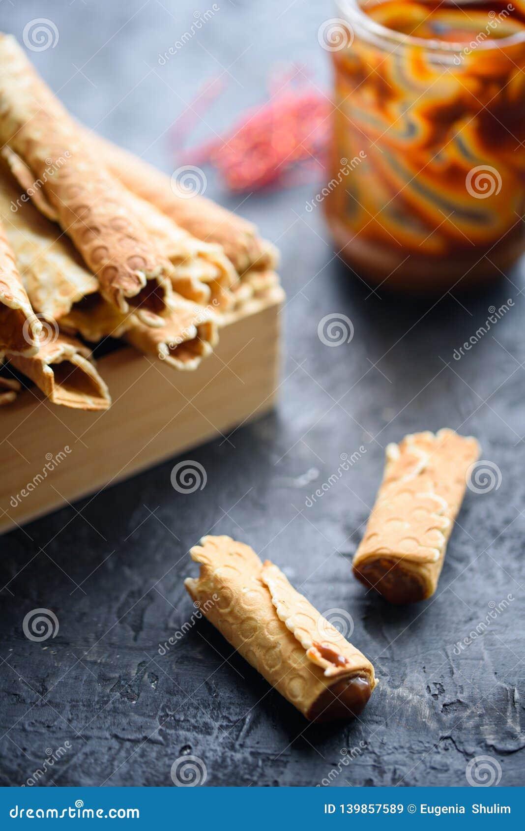 Het wafeltje rolt, smakelijk en geurig, met gekookte condens op een zwarte lijst