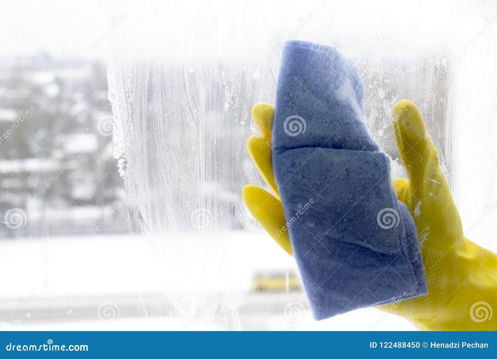 Het wassen van het venster in gele handschoenen, close-uphand