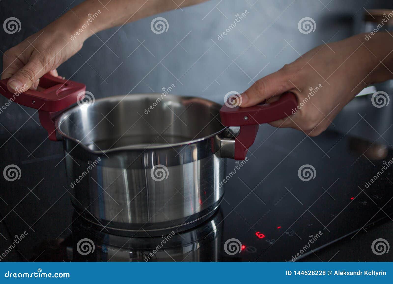 Het water in de pan is op de inductiehaardplaat Thuis het koken