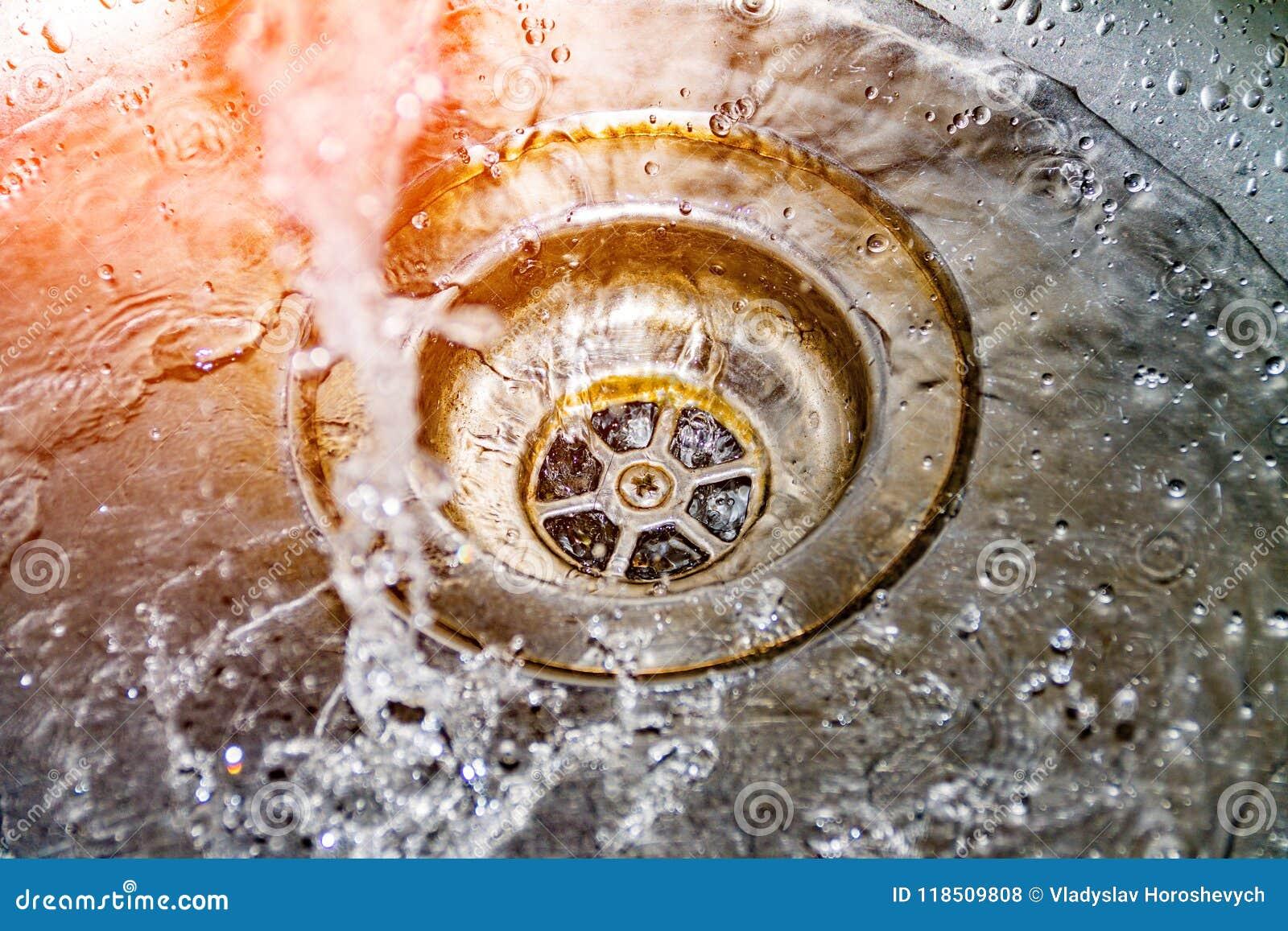 Het water voert in de gootsteen, gootsteen af en het lopende water voor de achtergrond, behandelt het water