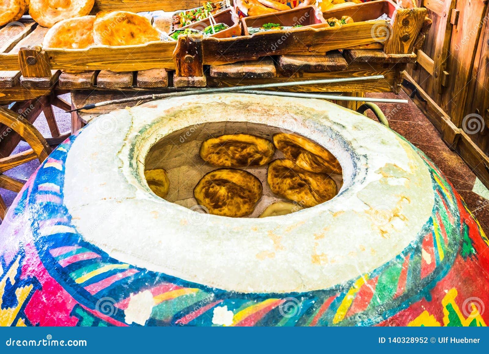 Het Weergeven op huis maakte lavash brood wordt gebakken binnen een traditionele Armeense geroepen vloeroven tonir