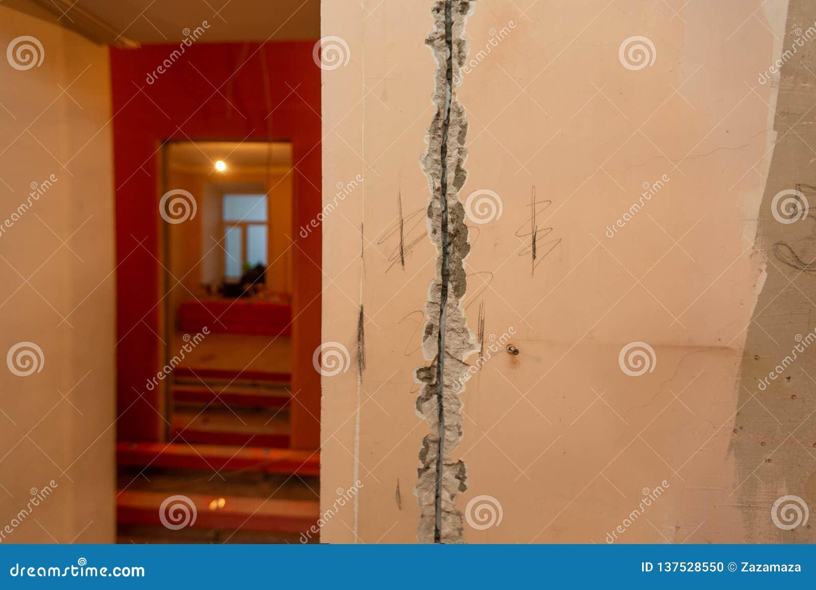 Het werk proces aan groef of muur die voor elektro, Internet-kabels en elektrische afzet achtervolgen alvorens te pleisteren en