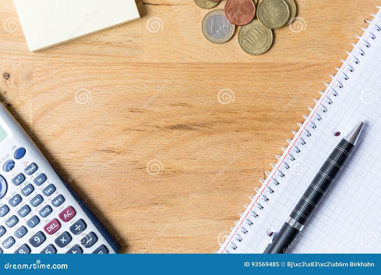 Het werkbureau met notastootkussen, calculator, biro en muntstukken op houten Ta