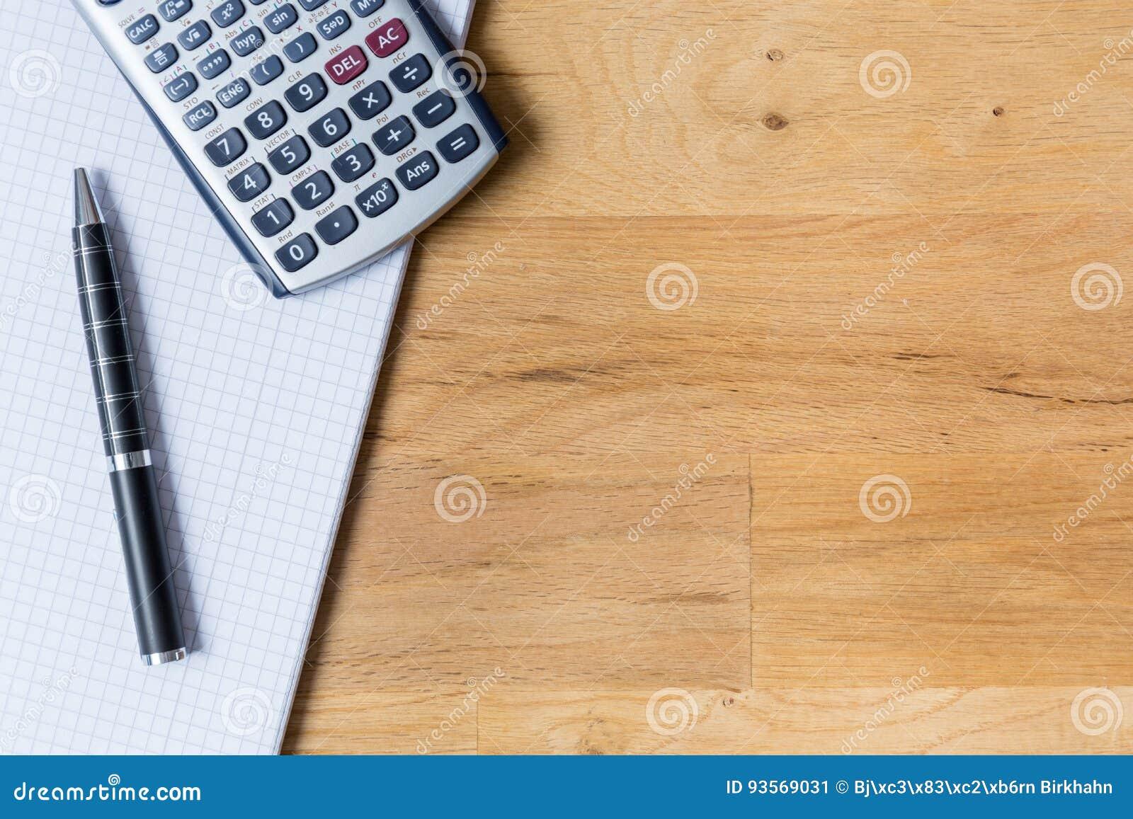 Het werkbureau met notastootkussen, calculator en biro op houten lijst