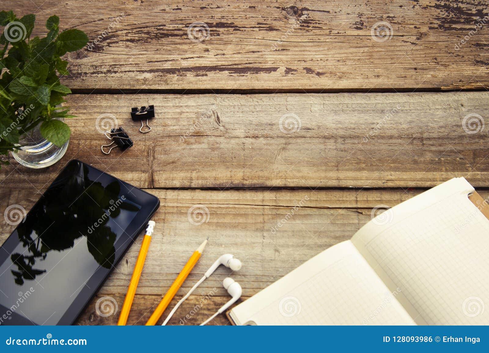 Het werklijst met het ipadscherm, de open groene bladeren van notitieboekjeang De ruimte van het exemplaar Rustieke houten achter