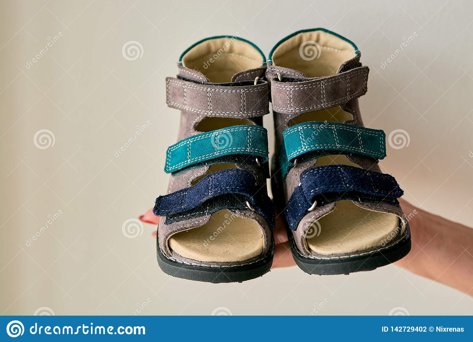 Het wijfje houdt close-up een orthopedische die de schoensandals van speciale kinderen van echt leer wordt gemaakt