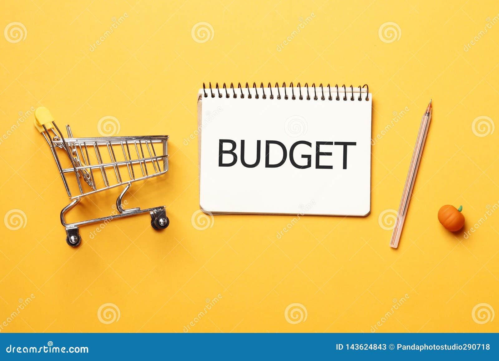 Het winkelen concept Het concept van de begroting Boodschappenwagentje, leeg document notitieboekje met pen op een gele achtergro