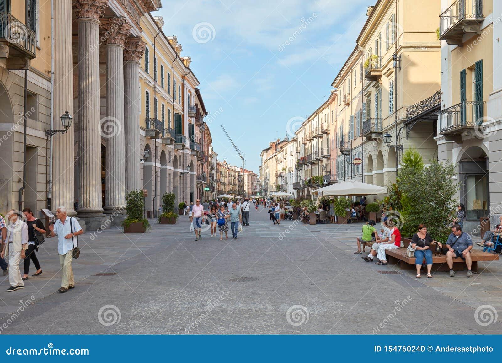 Het winkelen straat via Rome met mensen en historische gebouwen die in Cuneo, Italië lopen