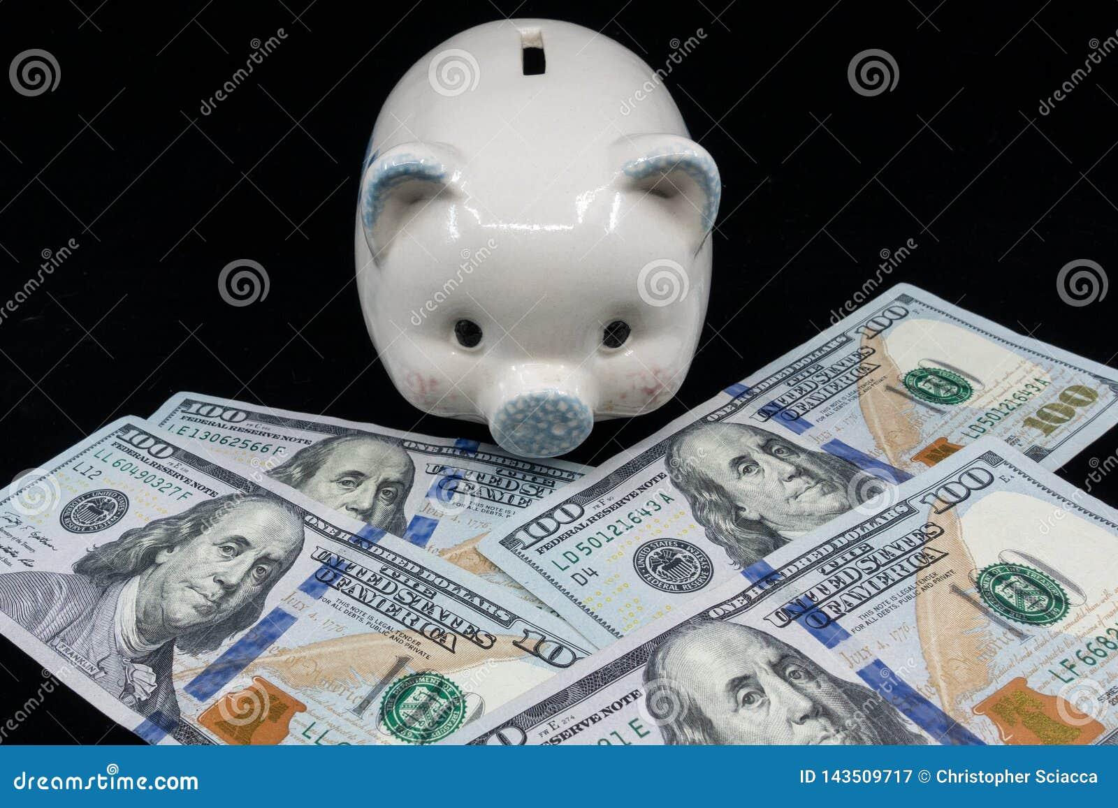 Het witte spaarvarken isoleerde close-up op een stapel van de munt van Verenigde Staten tegen een zwarte achtergrond Rijkdom en b