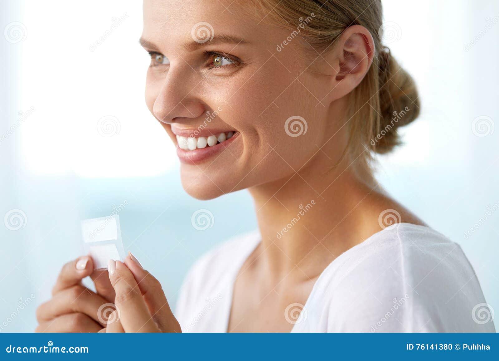 Het witten van tanden Mooie Glimlachende Vrouwenholding die Strook witten
