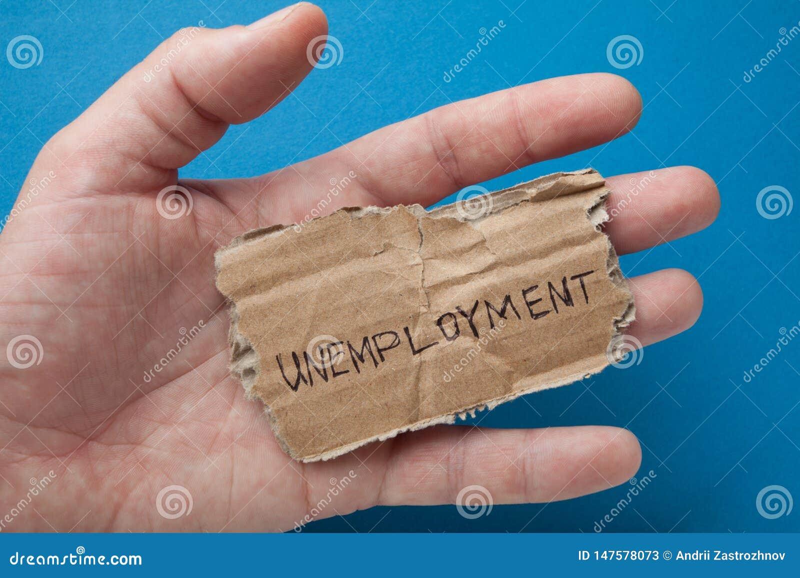 Het woord 'werkloosheid 'op het gescheurde oude karton in de hand van een mens
