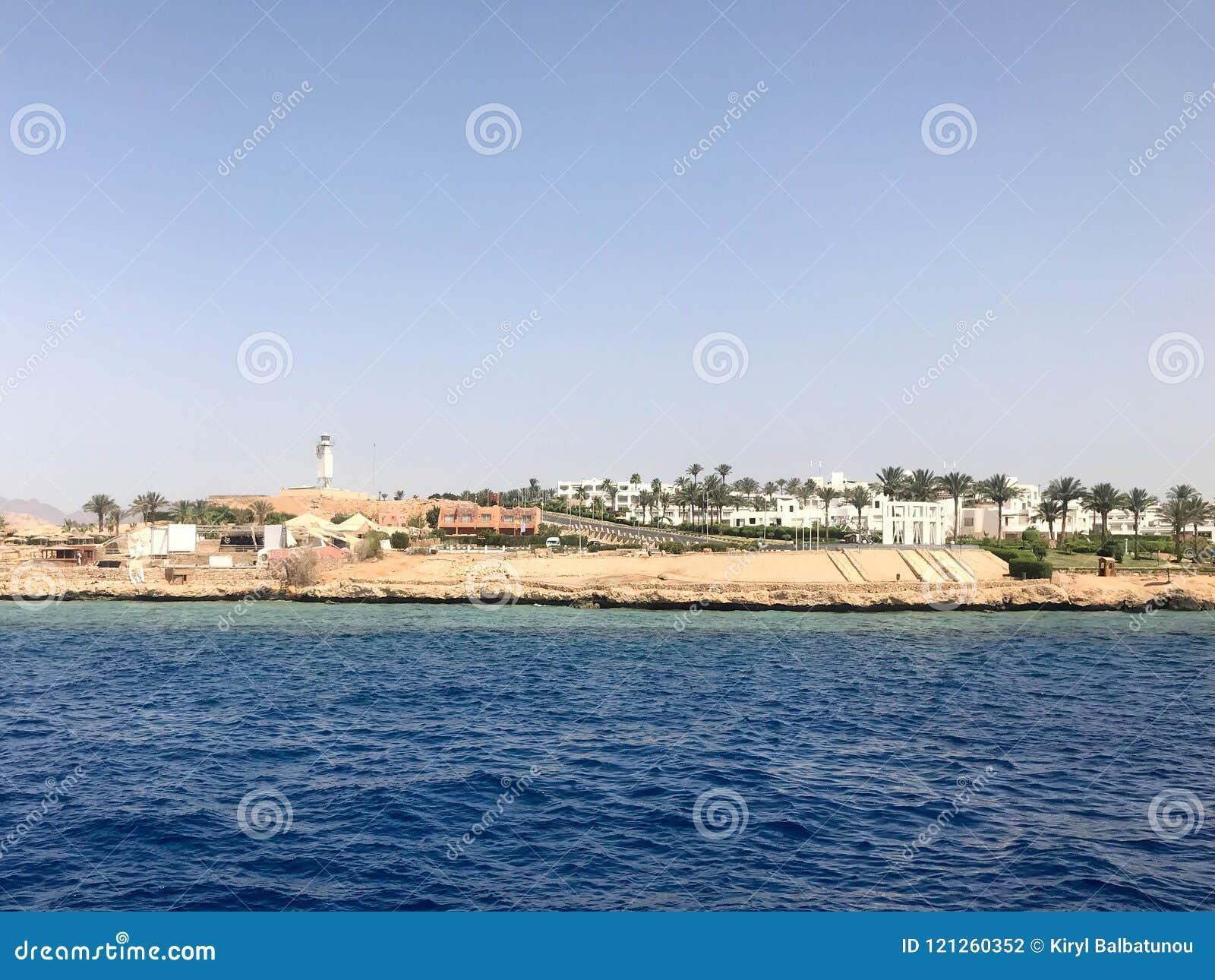 Het zeegezicht van de verre mooie bruine steenbergen en de diverse gebouwen op de kust en het blauwe zoute azuurblauwe overzees,