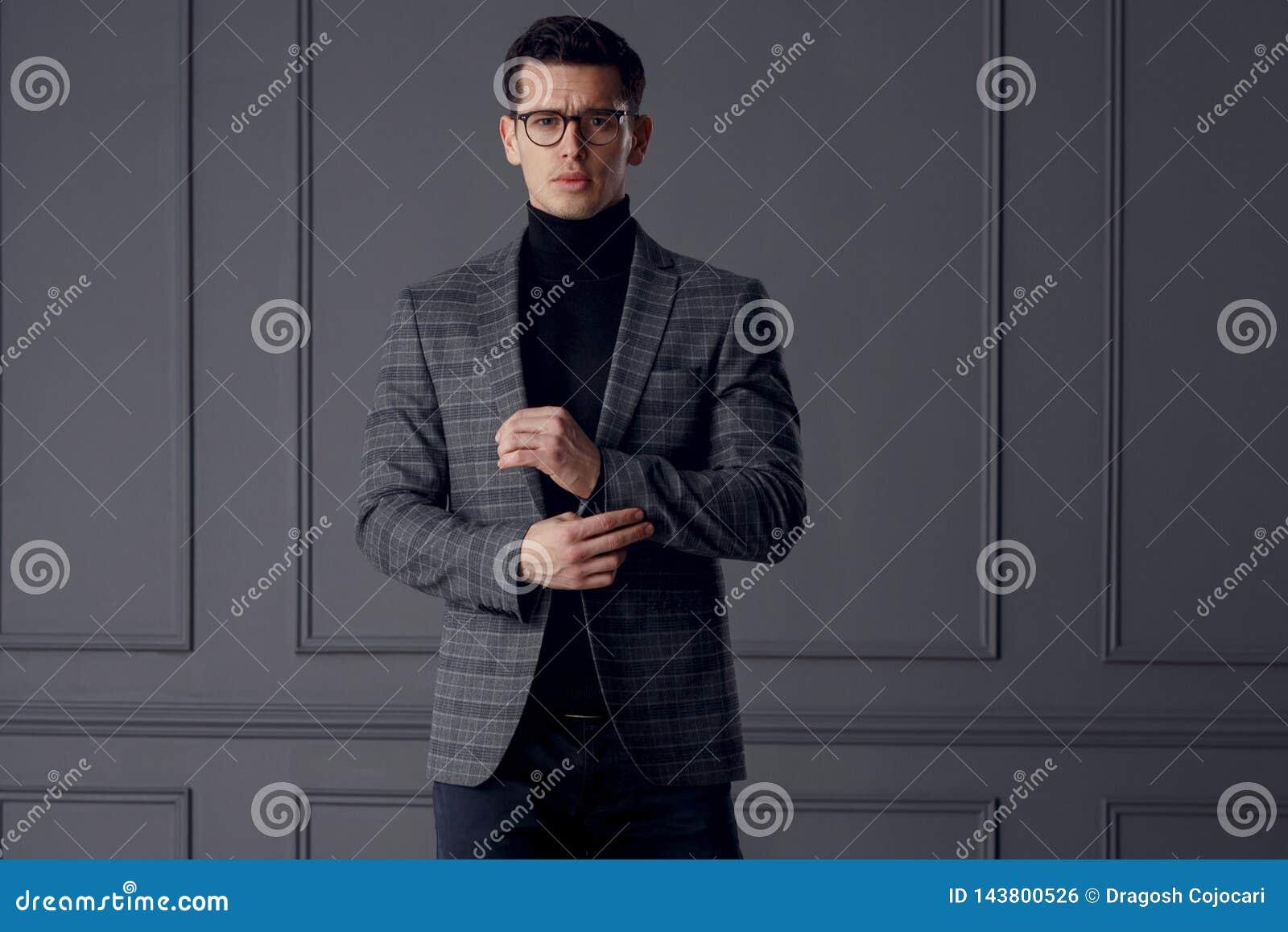 Het zekere bussinesman slijtage modieuze grijze kostuum en de zwarte oogglazen kijken met houding, op grijze muurachtergrond