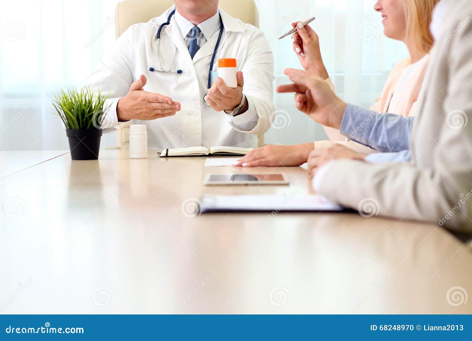 Het ziekenhuis, medisch onderwijs, gezondheidszorg, mensen en geneeskundeconcept - arts die meds aan de groep gelukkige artsen bi
