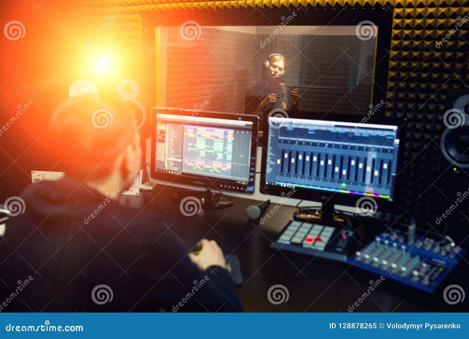 Het zingende meisje zingt aan de professionele microfoon in de verslagstudio Het proces van leidt tot een nieuw klaplied door jon