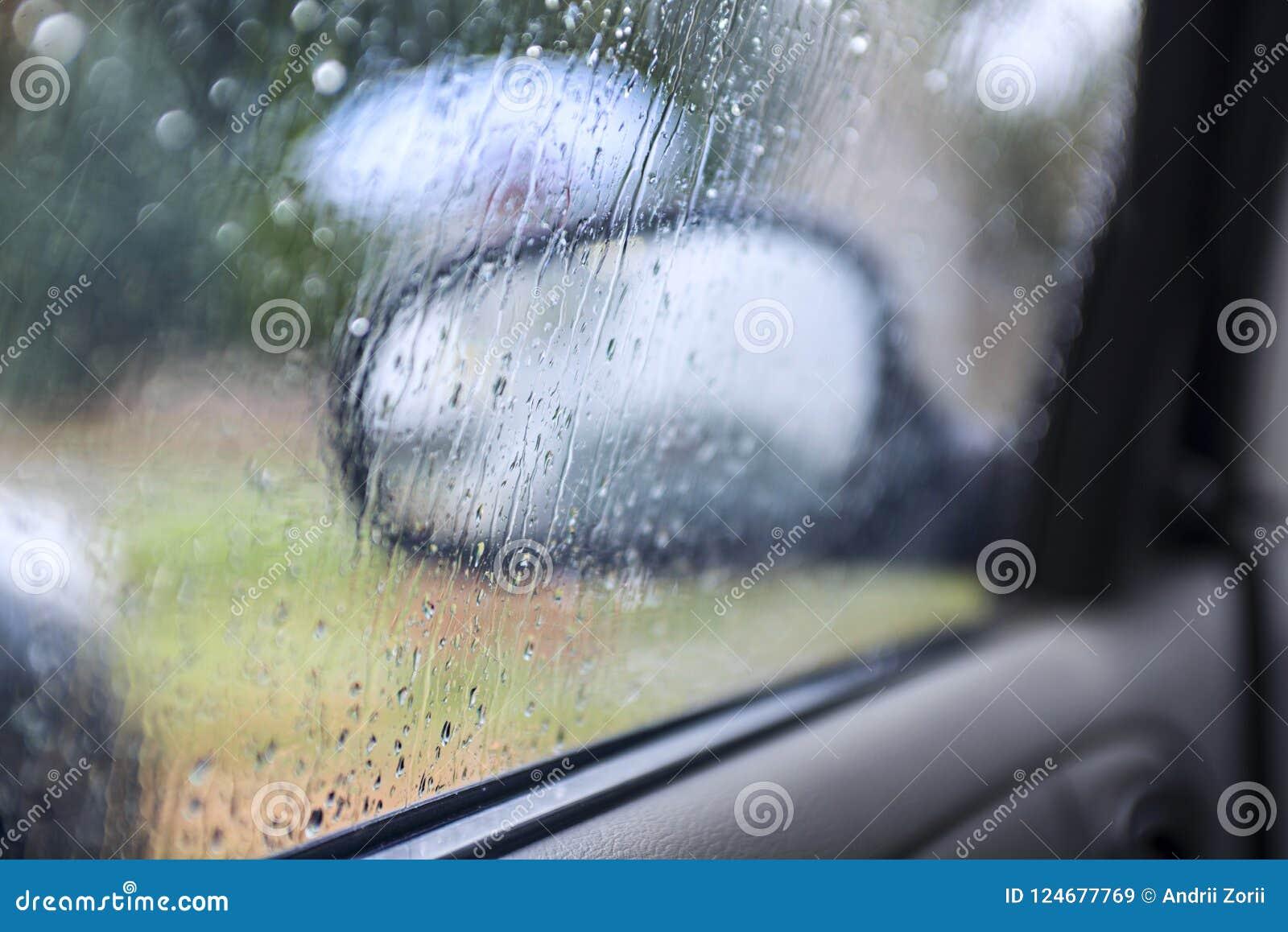 Het zitten in auto` s cabine terwijl buiten het regenen de regendaling is nog op het vensterglas