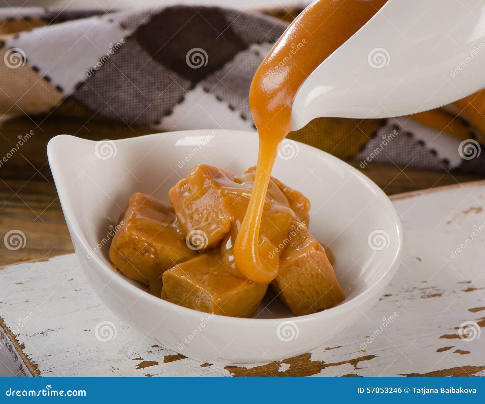 Het zoete Karamelsaus gieten in een witte kom