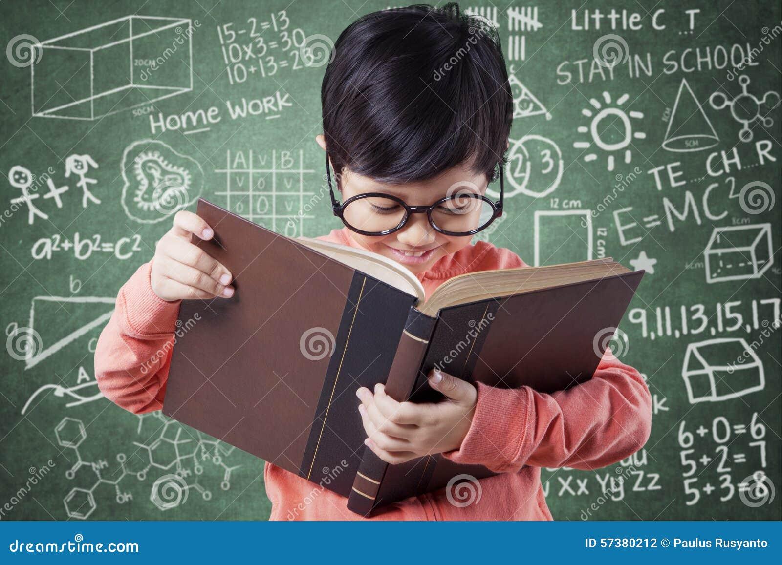 Het zoete meisje leert met boek dichtbij bord