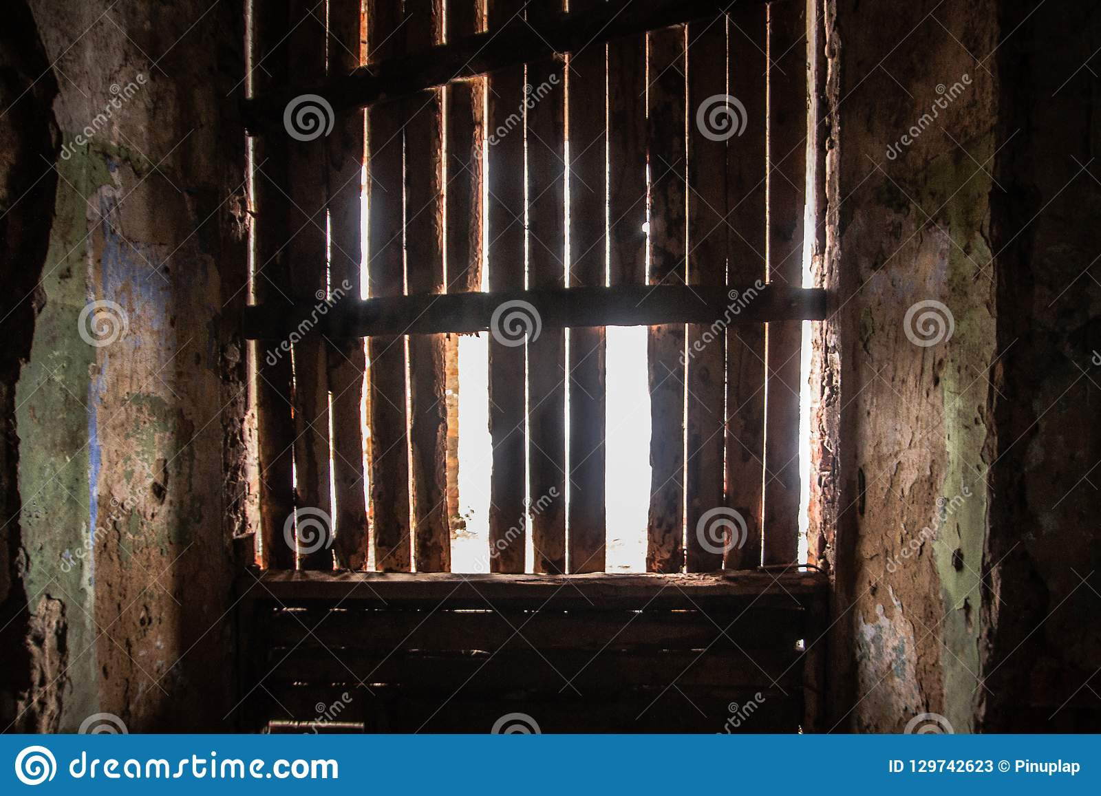 Het zonlicht doordringt het onderdrukte venster in de oude donkere ruimte