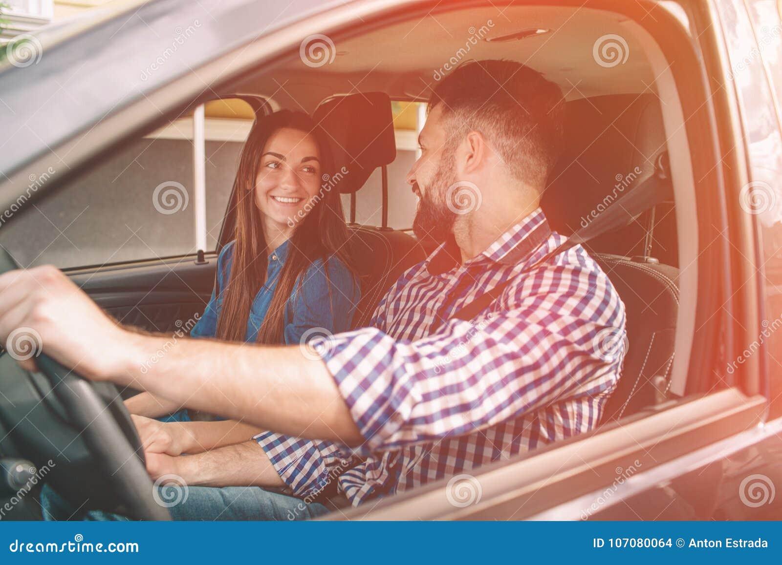 Het zorgvuldige drijven Mooie jonge paarzitting op de voorpassagierszetels en het glimlachen terwijl knappe mens die a drijven