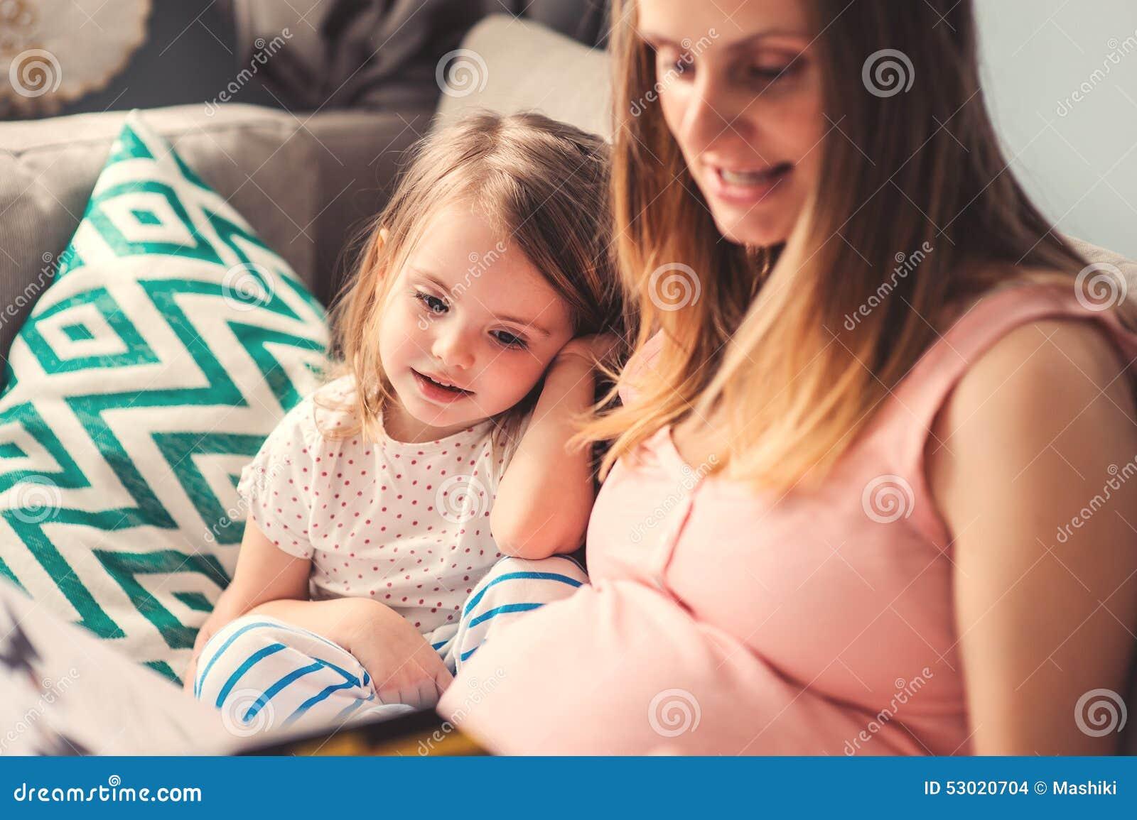 Het zwangere boek van de vrouwenlezing aan haar gelukkige peuterdochter thuis