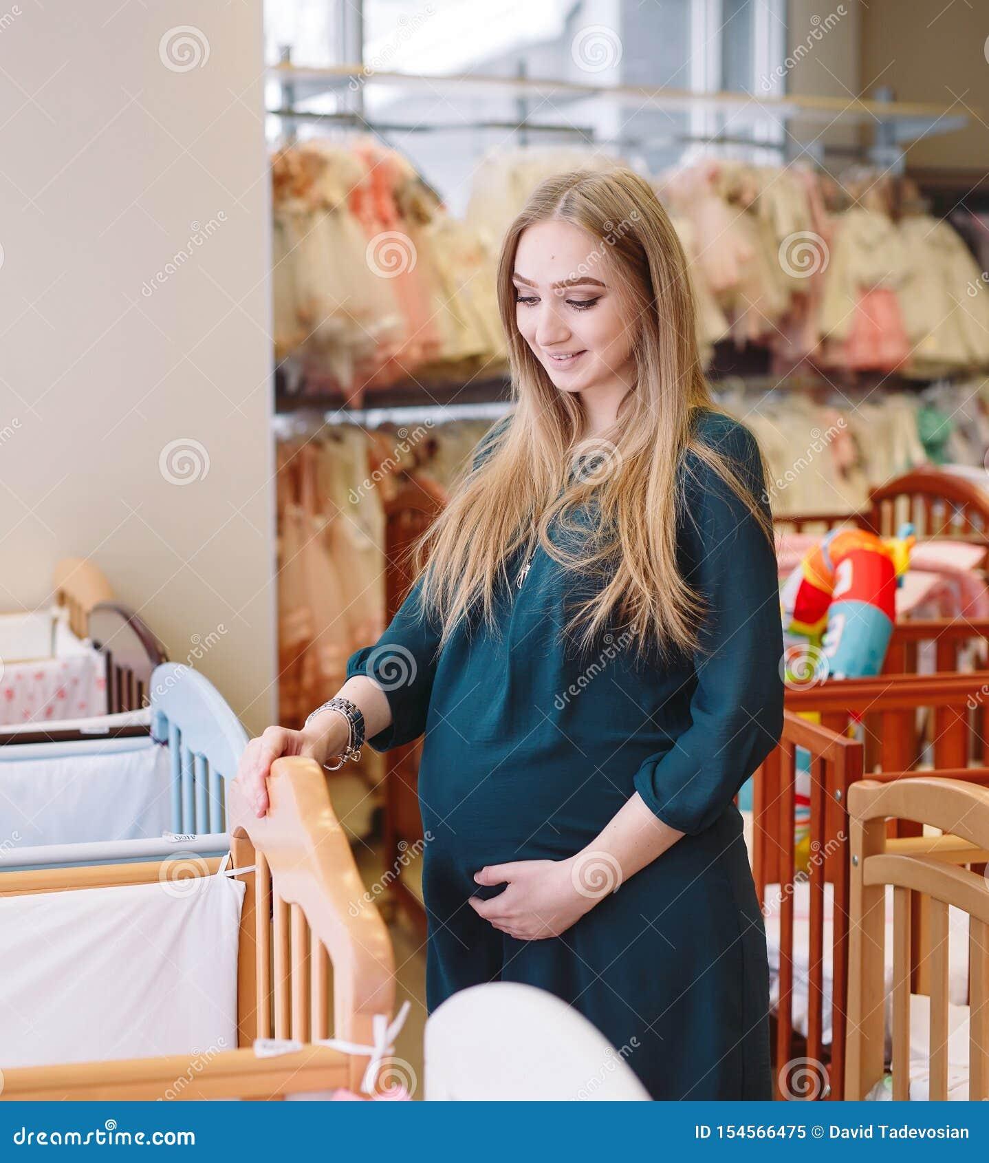 Het zwangere meisje kiest een babywieg in de opslag